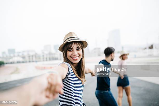 Spain, Barcelona, portrait of smiling young woman holding hands with her friends