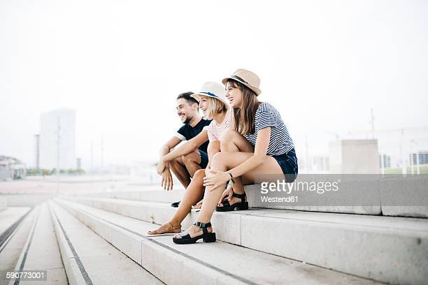 Spain, Barcelona, three laughing friends sitting side by side on stairs