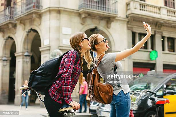 Spain, Barcelona, two playful young women taking a selfie
