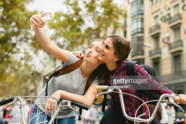 Spain, Barcelona, two young women on bicycles taking a selfie
