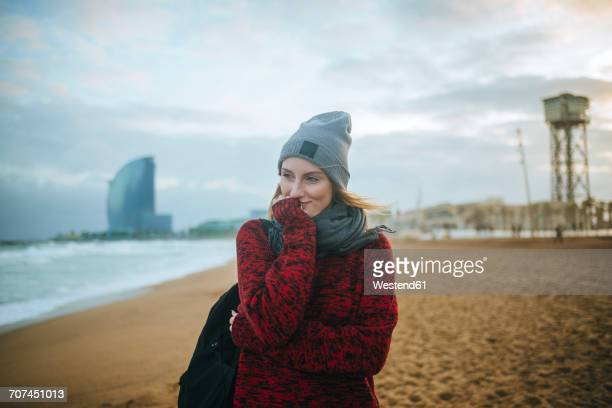 Spain, Barcelona, young woman on the beach in winter