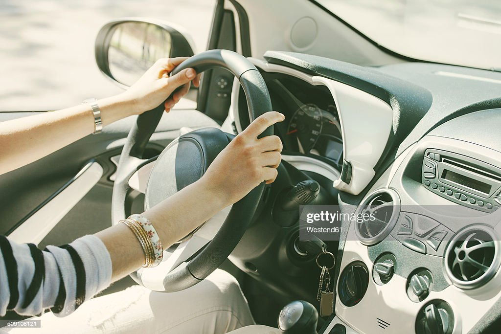 Spain, Barcelona, Young woman steering car