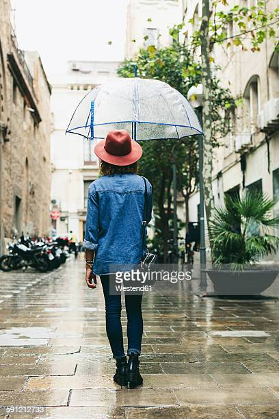 Spain, Barcelona, young woman with umbrella wearing hat and denim shirt