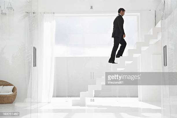 Spain, Businessman cimbing up stairs