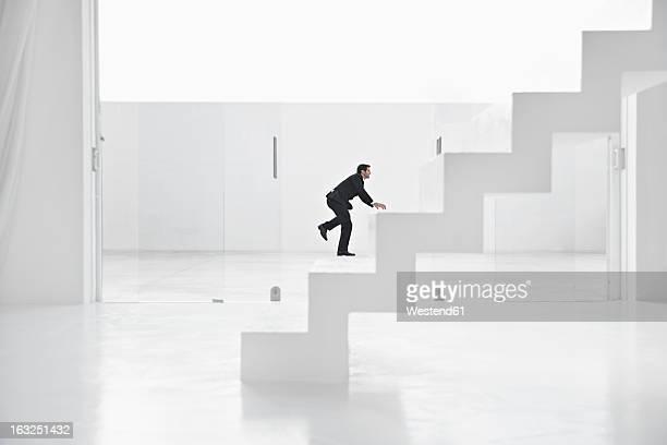 Spain, Businessman climbing up ladders