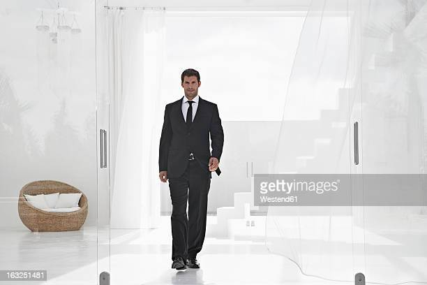 Spain, Businessman walking through living room, stairs in background