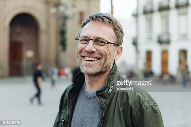 Spain, Canary Islands, Gran Canaria, Las Palmas, portrait of laughing mature man in front of Catedral de Santa Ana