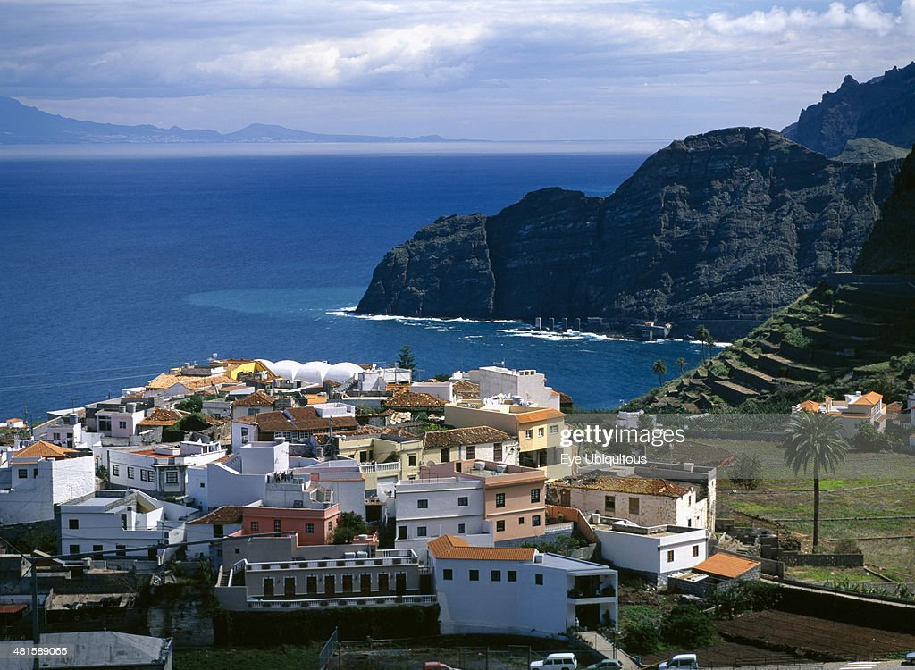 Spain Canary Islands La Gomera Agulo White yellow and orange painted houses with tiled rooftops terraced hillside volcanic cliffs and sea beyond