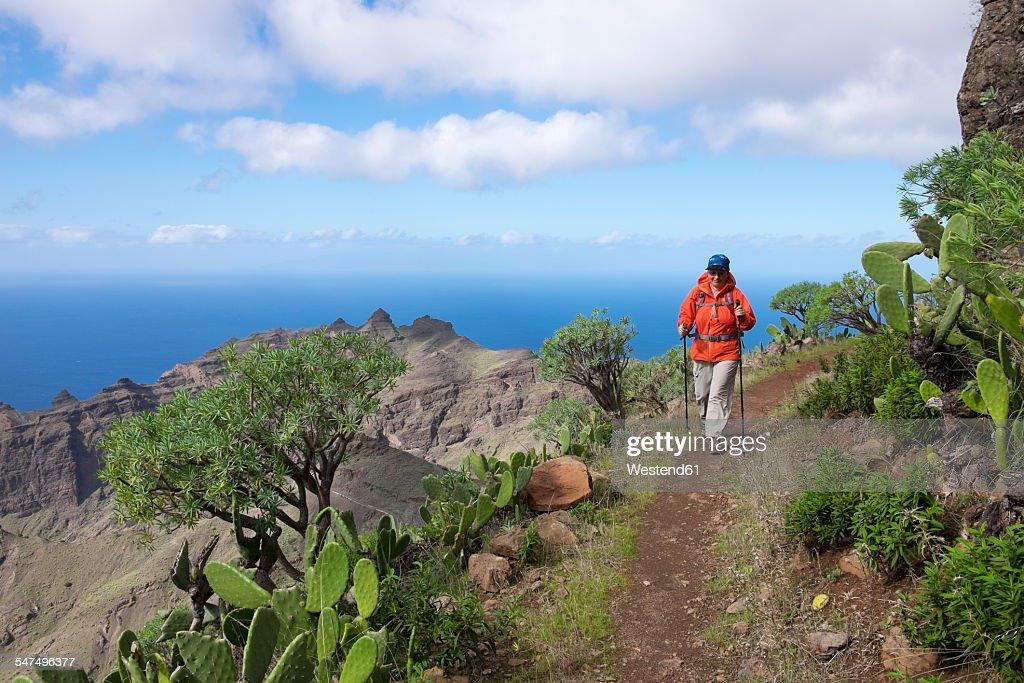 Spain, Canary Islands, La Gomera, Valle Gran Rey, trail and hiker in Lomo del Carreton near Arure