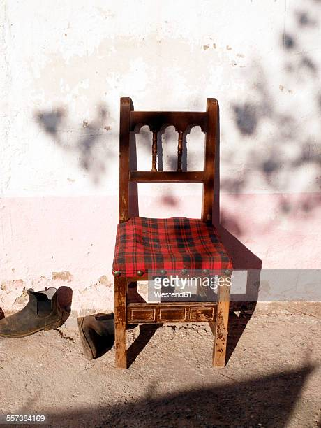 Spain, Catalonia, chair in pair of boots at sunlight