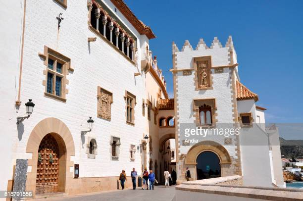 Sitges Tourists along the Maricel del Mar Palace Museum with its white walls