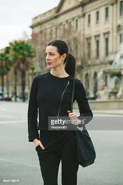 Spain, Catalunya, Barcelona, young black dressed businesswoman in front of a street