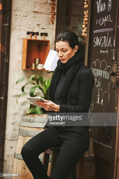 Spain, Catalunya, Barcelona, young black dressed businesswoman looking at her smartphone in front of a wine bar