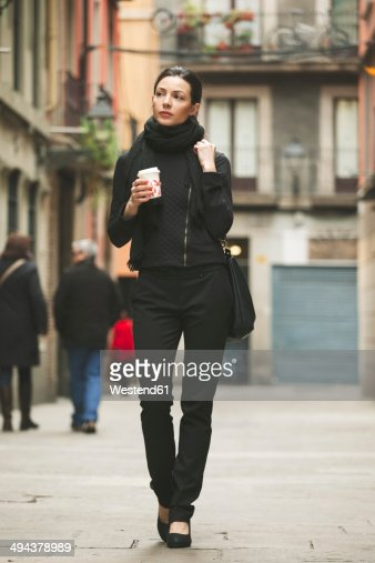 Spain, Catalunya, Barcelona, young black dressed businesswoman with coffee to go in front of a street