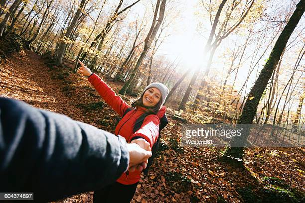 Spain, Catalunya, Girona, smiling woman in the woods holding mans hand