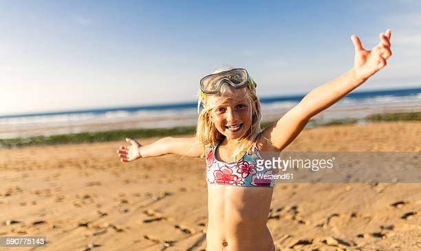 Spain, Colunga, portrait of smiling blond little girl with diving mask and arms outstretched on the beach