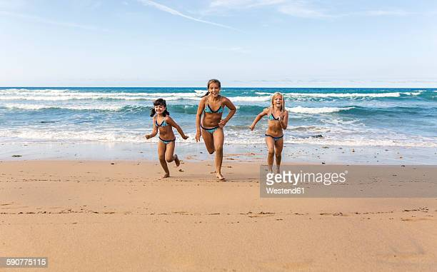 Spain, Colunga, three girls running side by side on the beach