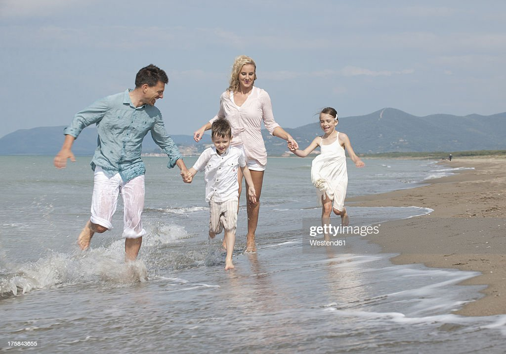 Spain, Family running on beach : Stock Photo