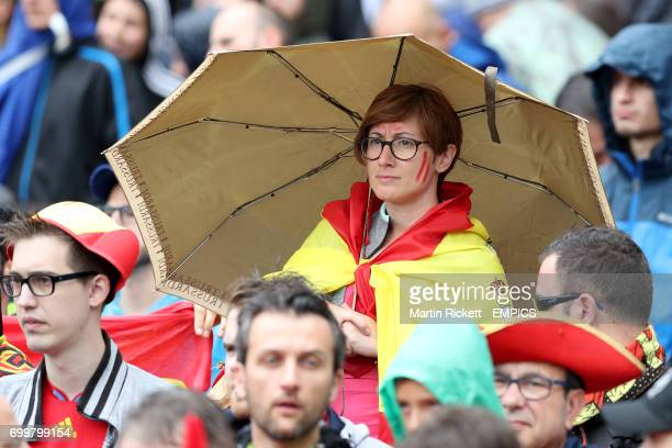A Spain fan shelters from the rain under her umbrella inside the Stadium de Toulouse before kick off
