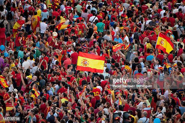 Spain fans fly the national flag as crowds of wait to celebrate with the players as they parade the UEFA EURO 2012 trophy on a doubledecker bus on...