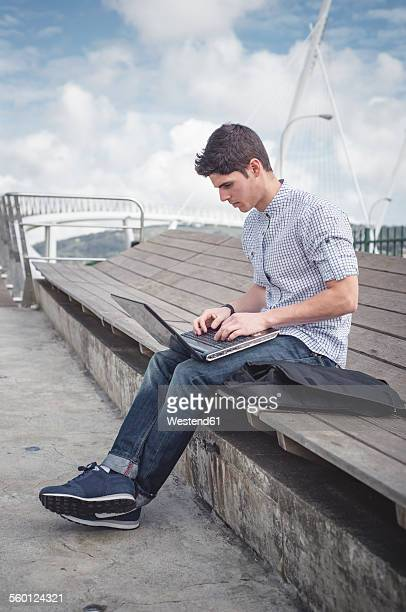 Spain, Ferrol, young man using a laptop outdoors