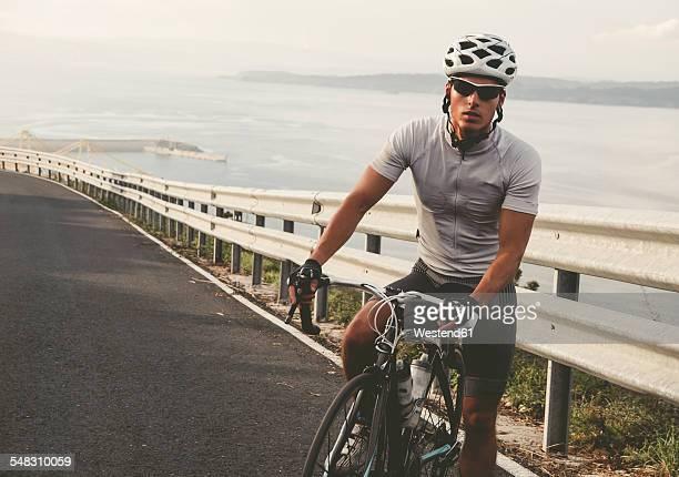 Spain, Galicia, Ferrol, cyclist on the road