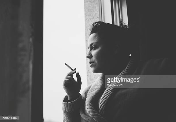 Spain, Galicia, Naron, Adult woman smoking in the window of her home