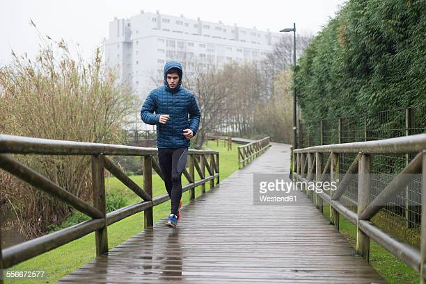 Spain, Galicia, Naron, runner on a promenade in park at a rainy day