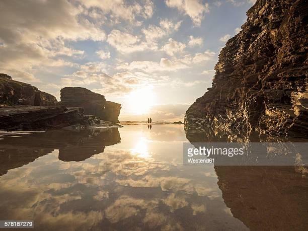 Spain, Galicia, Ribadeo, Playa de Aguas Santas at sunset, small people on the beach