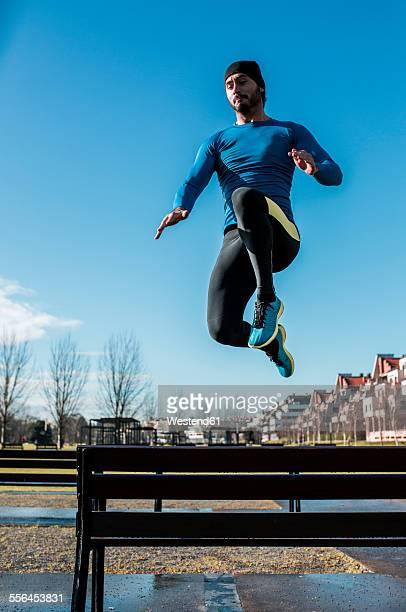 Spain, Gijon, athlete jumping over park bench