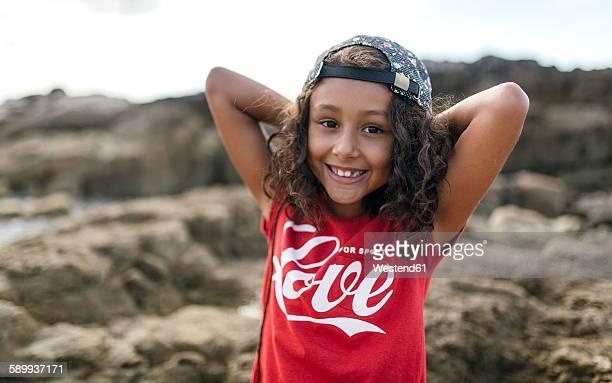 Spain, Gijon, portrait of smiling little girl at rocky coast