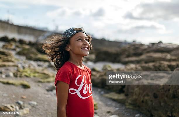 Spain, Gijon, portrait of smiling little girl on rocky beach looking up