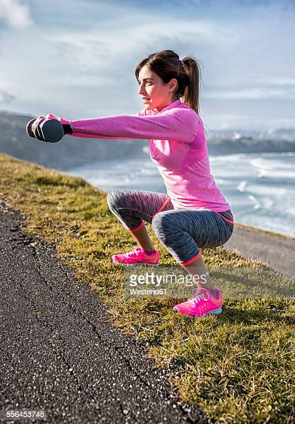 Spain, Gijon, sportive young woman doing workouts at the coast