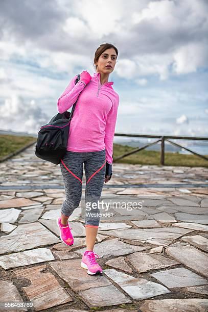 Spain, Gijon, sportive young woman walking outdoors