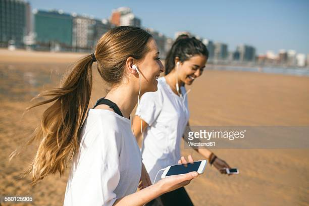 Spain, Gijon, two sportive young women with earbuds on the beach