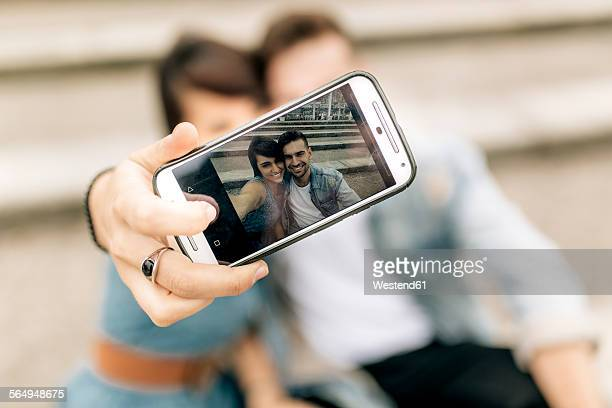 Spain, Gijon, young couple in love taking selfie with smartphone