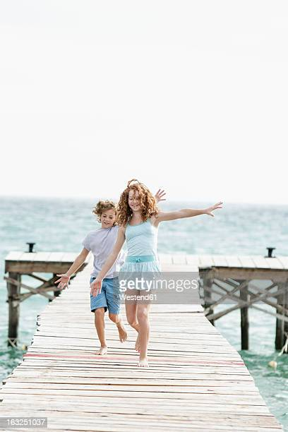 Spain, Girl and boy running on jetty at he sea