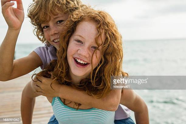 Spain, Girl giving piggy ride to boy, smiling