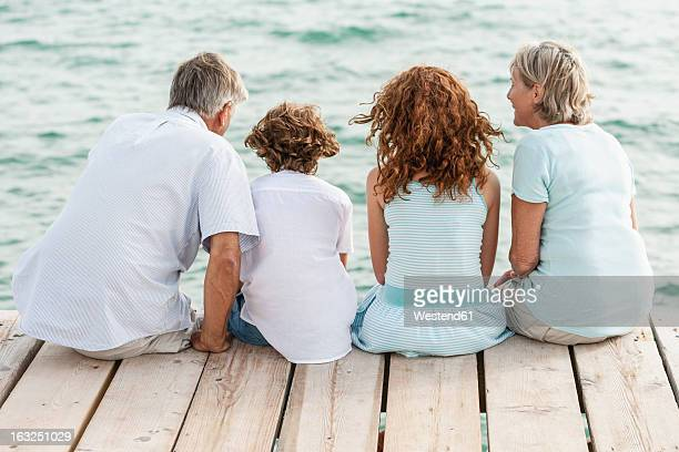 Spain, Grandparents with grandchildren sitting on jetty