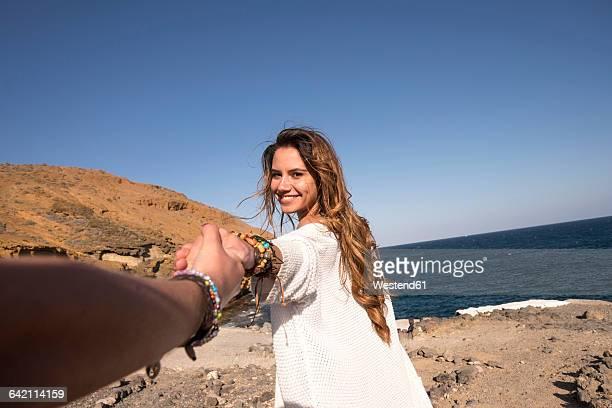 Spain, happy teenage girl holding hand of her friend