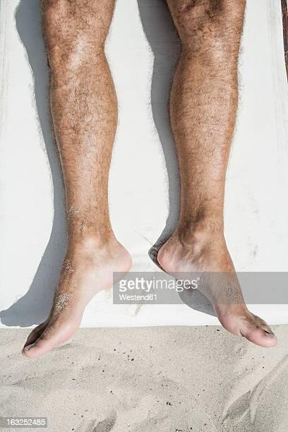 Spain, Human legs on beach towel