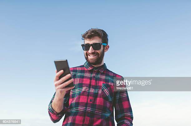 Spain, La Coruna, portrait of smiling hipster with sunglasses looking at his phablet in front of blue sky