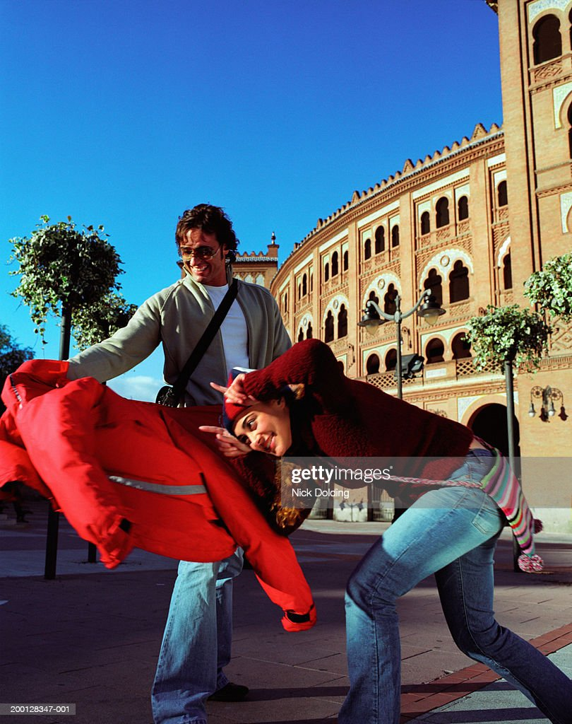 Spain, Madrid, couple 'bullfighting' outside Las Ventas bullring : Stock Photo