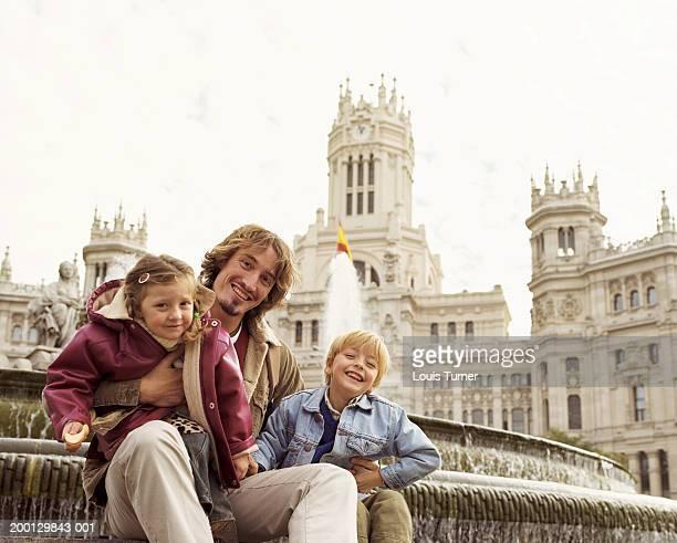 Spain, Madrid, Plaza de la Cibeles, man and children (3-6), portrait