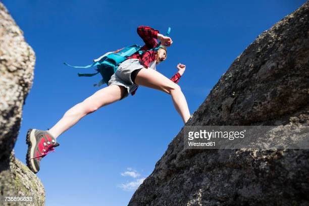 Spain, Madrid, young woman jumping between rocks during a trekking day
