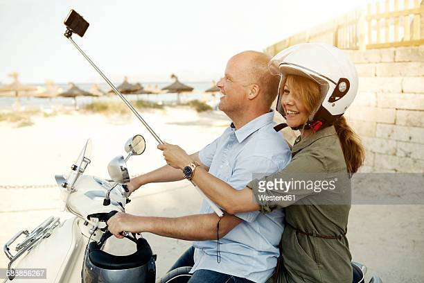 Spain, Majorca, Alcudia, couple with selfie stick on motor scooter