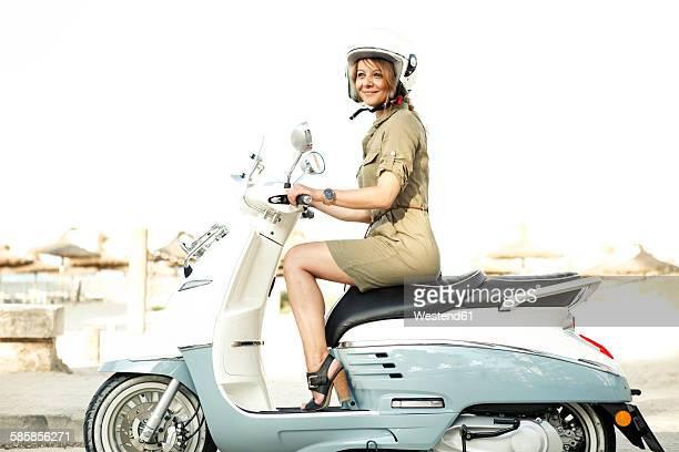 Spain, Majorca, Alcudia, woman on motor scooter