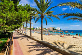 Beach resort of Magaluf on Mallorca island, promenade and beach with palm trees.