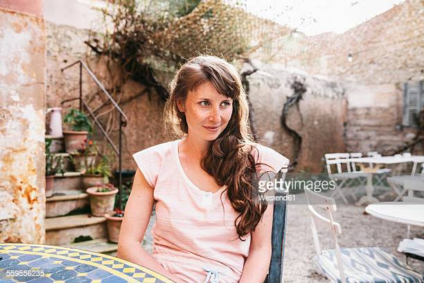 Spain, Mallorca, Arta, portrait of woman sitting at courtyard of a cafe