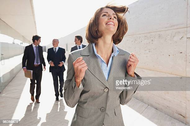 Spain, Mallorca, Businesswoman clenching fists, businessmen walking in background